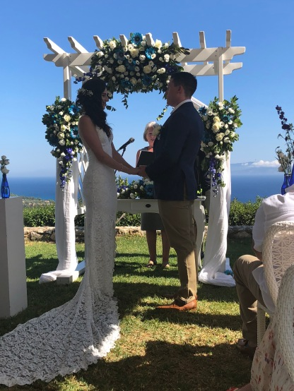 Ellie and Matt at the alter with flowers and blue sea view Lourdas Kefalonia