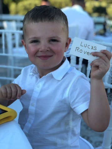 Lucas holding a sign with his name on